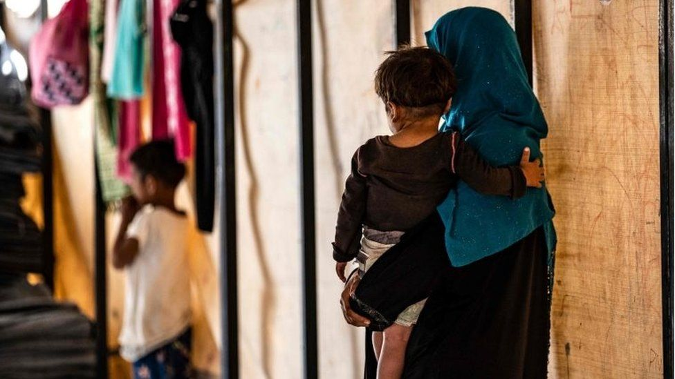 Sara al-Abdullah carries an orphan at a camp in the northern Syrian village of Ain Issa, on 26 September 2019.