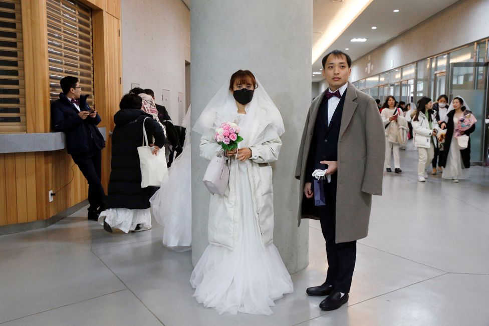 A bride wearing a mask for protection from the new coronavirus, attends a mass wedding ceremony of the Unification Church at Cheongshim Peace World Centre in Gapyeong,