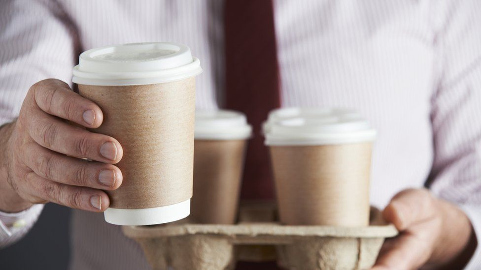 Man holding a tray of takeaway coffee