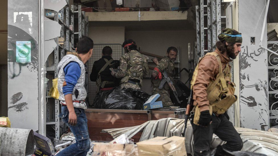 Turkish-backed Syrian rebel fighters loot a shop in the Syrian city of Afrin (18 March 2018)