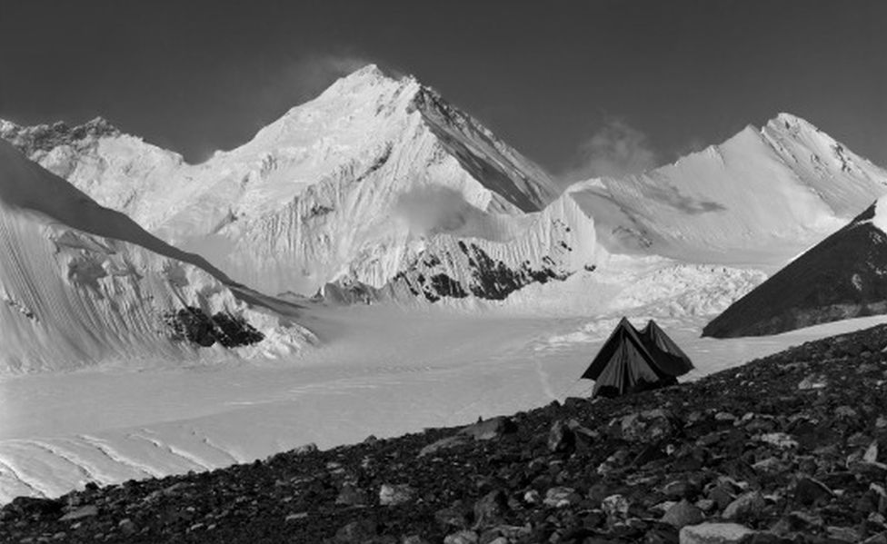 """A snowy mountain shot including a small old-fashioned tent, captioned, """"Camp at 20,000 feet - the last day"""""""