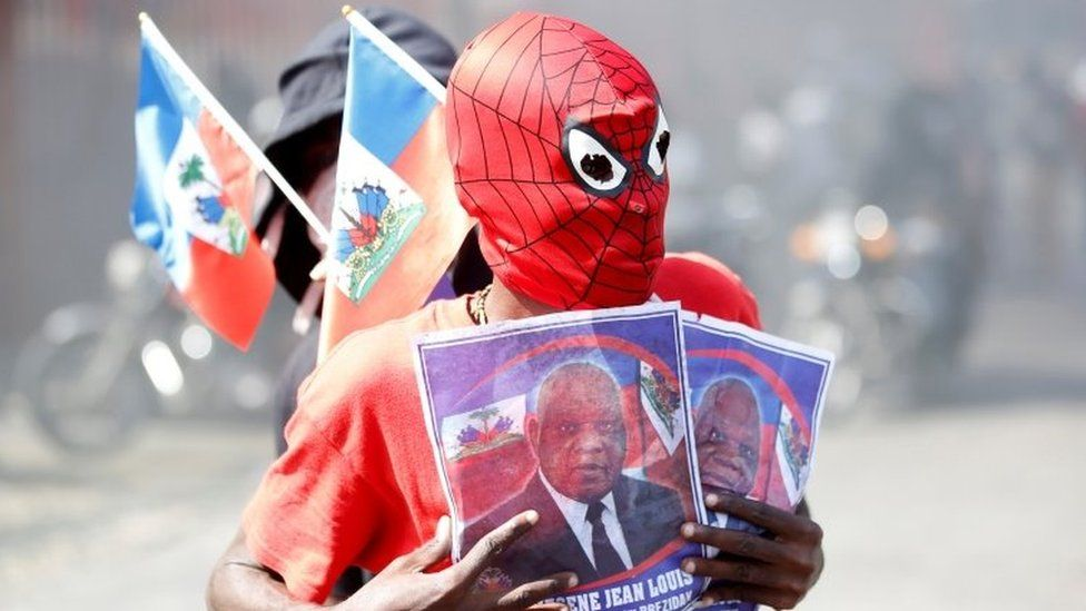 A demonstrator wearing a Spiderman mask holds photos of Supreme Court Judge Joseph Mecene Jean-Louis, as he takes part in a protest against Haiti's President Jovenel Moïse, in Port-au-Prince, Haiti February 14, 2021.