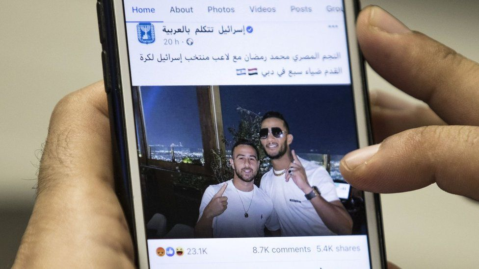 A man holds a mobile phone showing a Facebook post by the Israeli government featuring a photo of Egyptian singer Mohamed Ramadan and Israeli footballer Diaa Saba