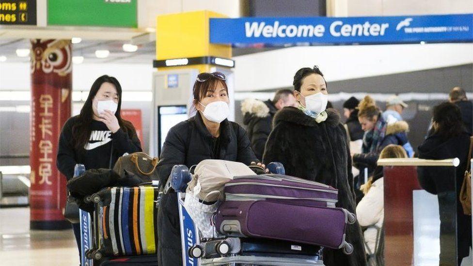 Visitors wearing medical masks arrive at New York's JFK airport