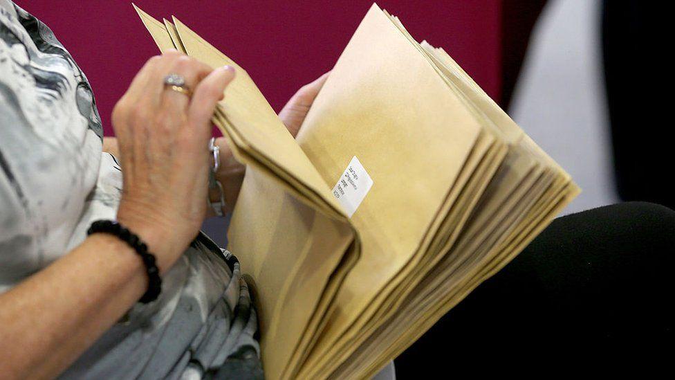 Teacher holding results envelopes