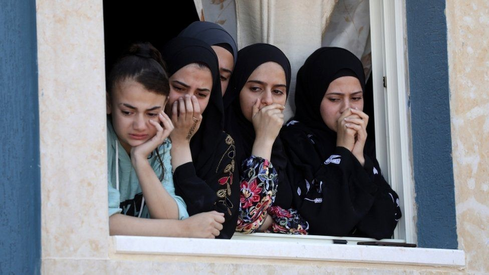 Palestinian relatives watch as mourners carry the body of Yaseen Hamad during his funeral in the West Bank on 16 May