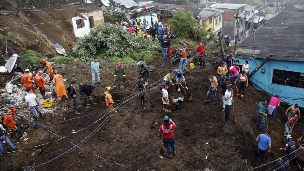 Rescue workers survey an area where a landslide destroyed several homes in Manizales