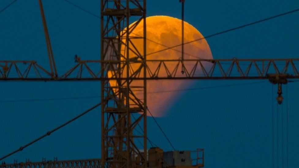 The moon standing in a partial lunar eclipse can be seen behind a construction crane on August 7, 2017 in Gilching, southern Germany.
