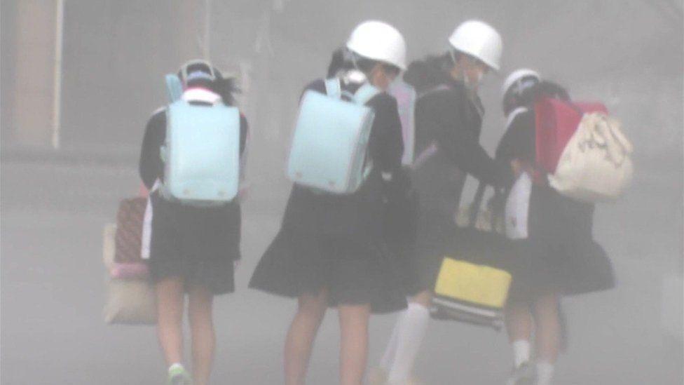 schoolgirls wearing helmets and face masks