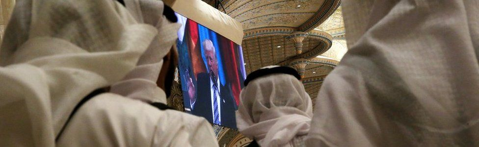 Tea servers watch US President Donald Trump deliver remarks to the Arab Islamic American Summit