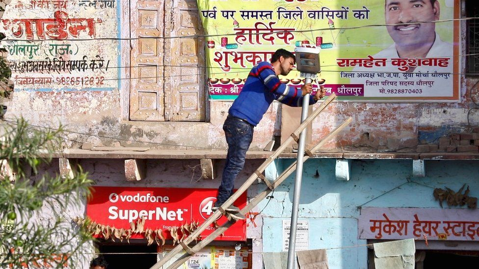 Solar powered street light being installed in a rural village in Rajasthan