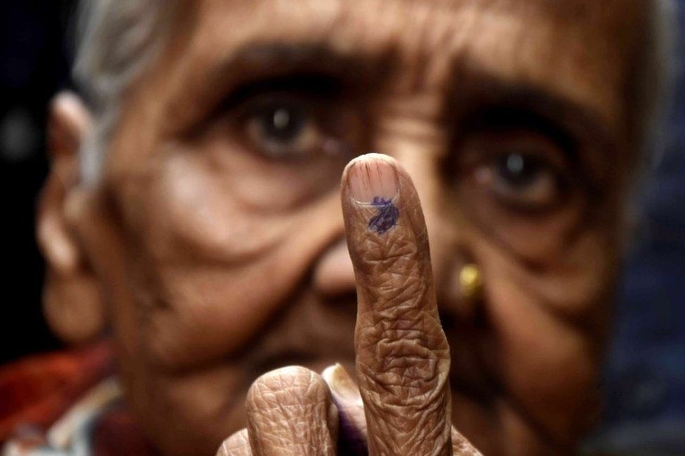 An Indian woman shows her ink marked finger after casting her vote at a polling station for the Madhya Pradesh state assembly elections in Bhopal, India, 28 November 2018