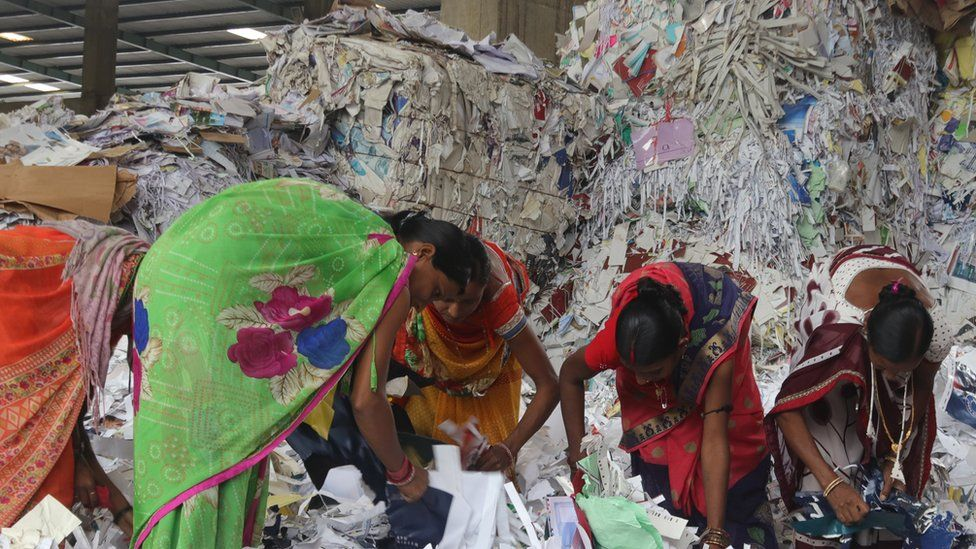 Women workers sort waste paper before it is recycled at a plant in Gujarat