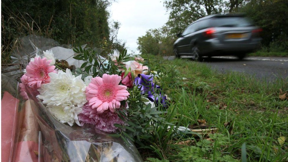 Floral tributes lay on the roadside near RAF Croughton in Northamptonshire, central England on October 10, 2019, at the spot where British motorcyclist Harry Dunn was killed