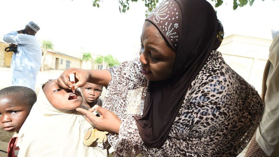 UNICEF health consultant Hadiza Waya (R) tries to immunise a child during vaccination campaign against polio at Hotoro-Kudu, Nassarawa district of Kano in northwest Nigeria, on April 22, 2017