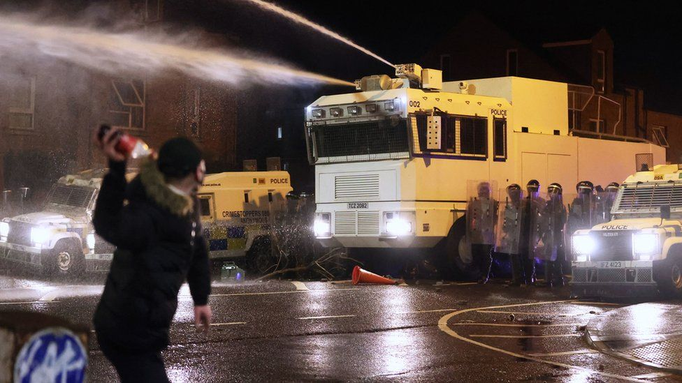 Objects are thrown towards PSNI officers and the water canon on Springfield Road in Belfast during further unrest