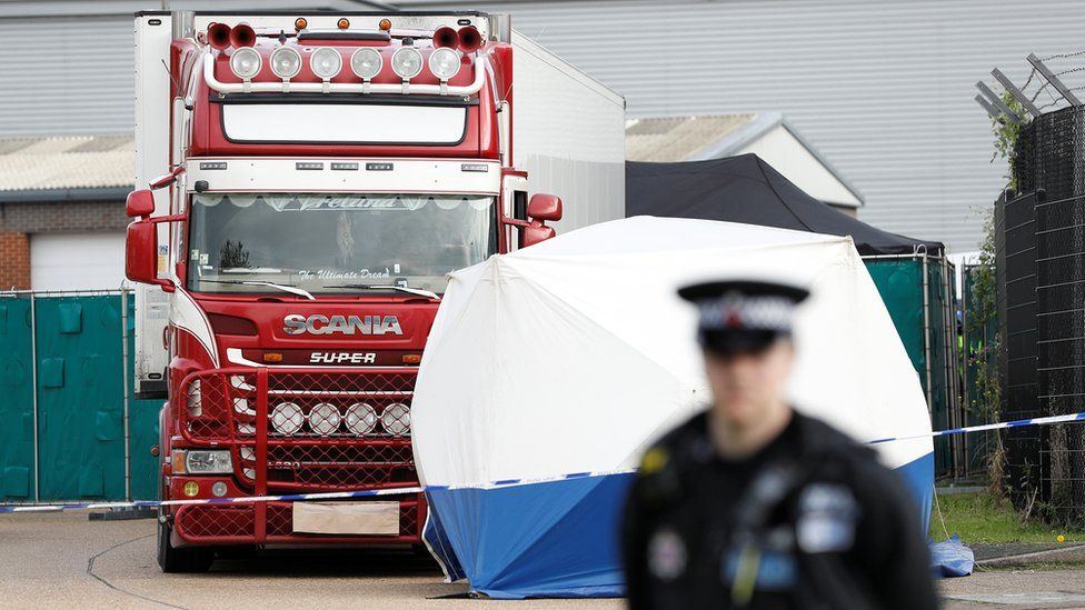Police officer and forensic tent near lorry