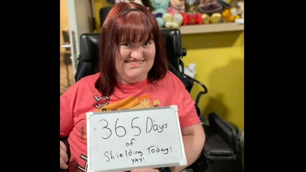 Michaela holding a sign which says '365 days of shielding today, yay' as taken on 12 March
