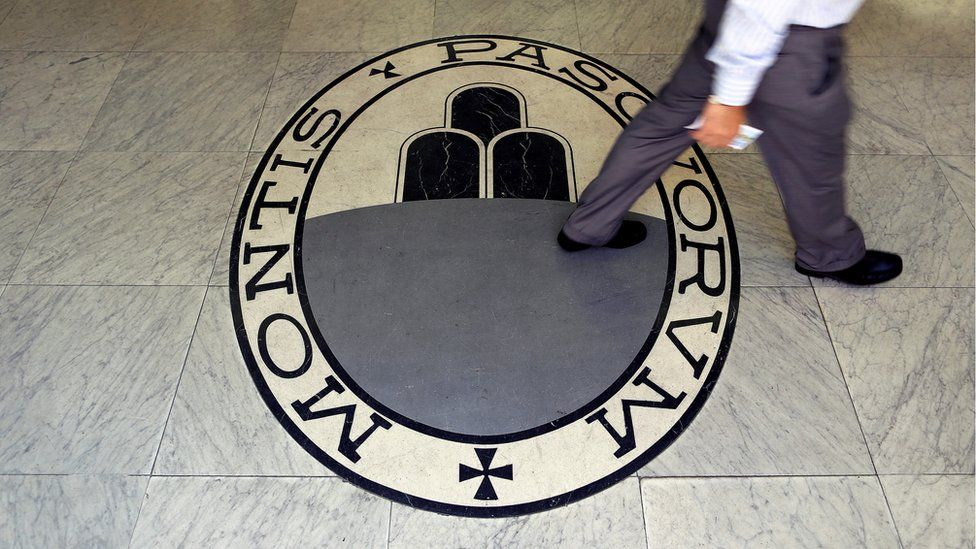 A man walks on a logo of the Monte Dei Paschi Di Siena bank in Rome