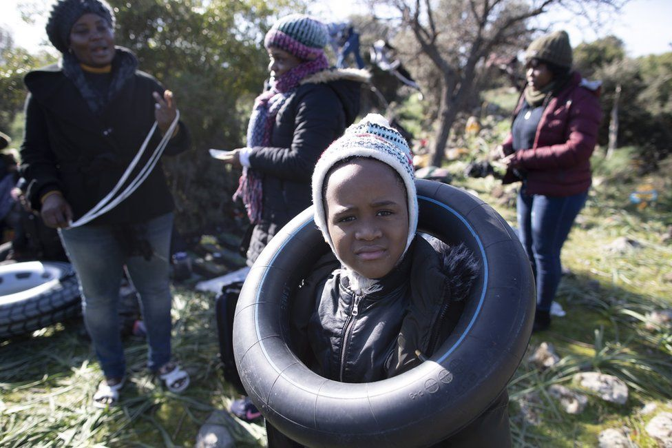 An African migrant boy plays with a rubber ring as they wait before attempting to cross the Aegean Sea by boat to reach the Greek island of Lesbos, in Ayvacik district, Canakkale region, Turkey, 3 March