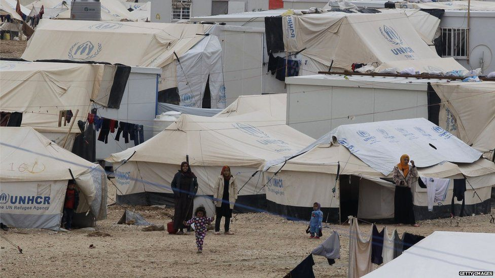 Syrian refugees standing next to tents at the UN-run Zaatari refugee camp, north east of the Jordanian capital Amman