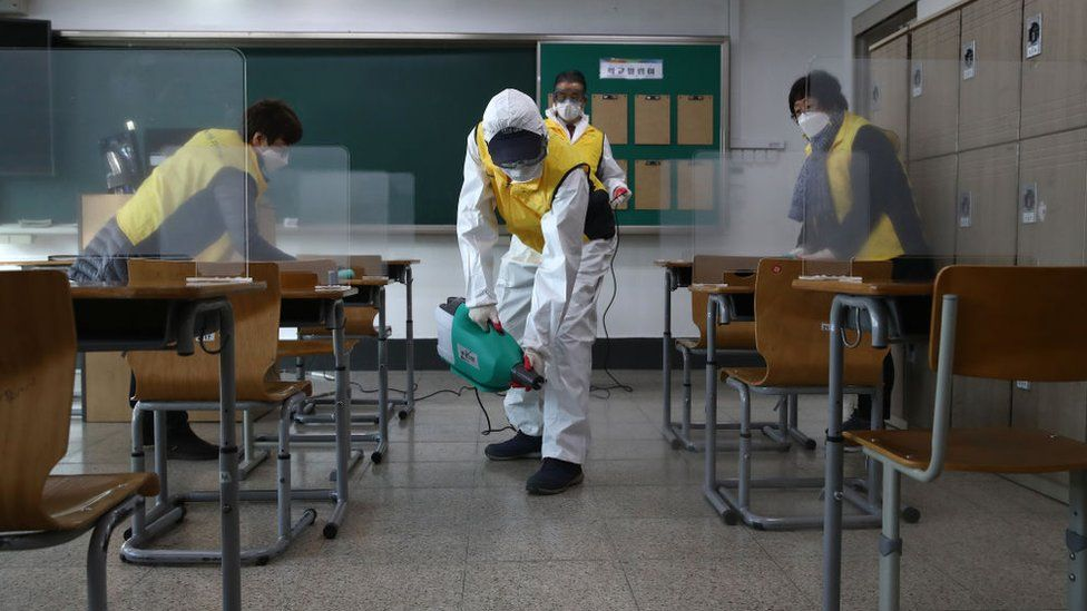 Workers disinfect a classroom in Seoul to prevent the spread of the coronavirus ahead of the exams