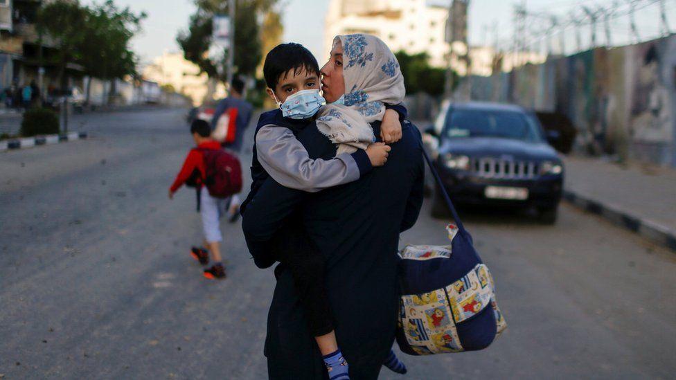 Seorang wanita Palestina menggendong putranya setelah gedung apartemen mereka terkena serangan udara Israel di Kota Gaza 12 Mei 2021