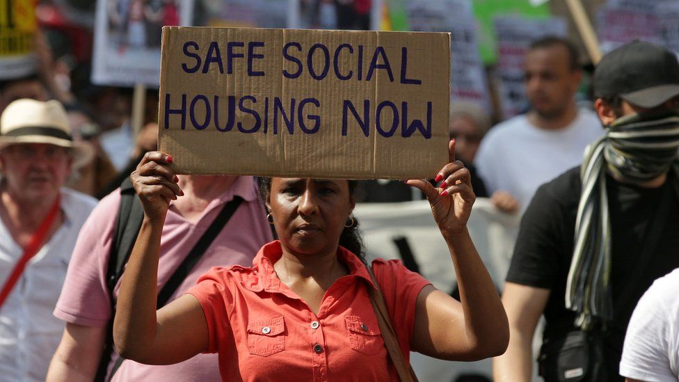 woman holds placard reading 'safe social housing now'
