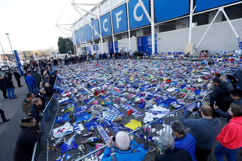 """People look at tributes left outside Leicester City""""s King Power stadium, on October 29th 2018"""