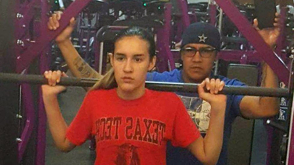 Adam helps his daughter Abby in the gym