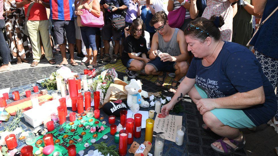A woman looks at the tribute to victims of the attack on Las Ramblas