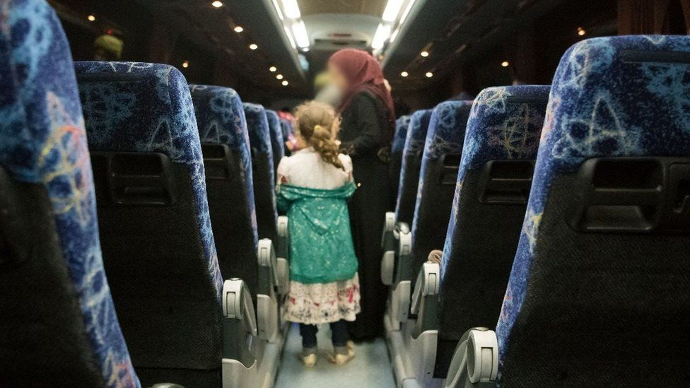 A woman and her child wait to get off the bus