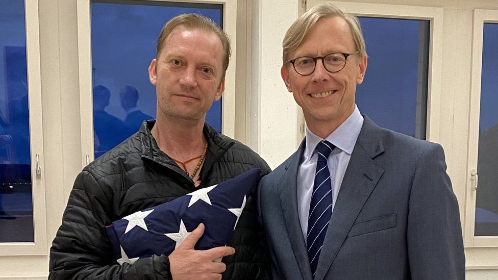 Michael White holds a US flag as he meets US Special Envoy to Iran Brian Hook at Zurich airport (4 June 2020)