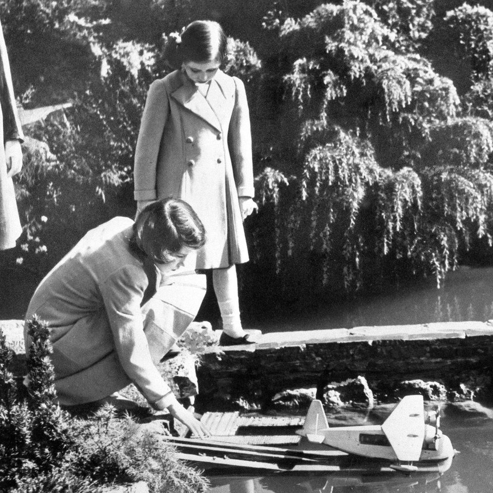 Princesses Elizabeth and Margaret launching a model seaplane at the Bekonscot model village in Beaconsfield, Buckinghamshire