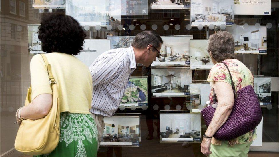 People outside estate agent's window
