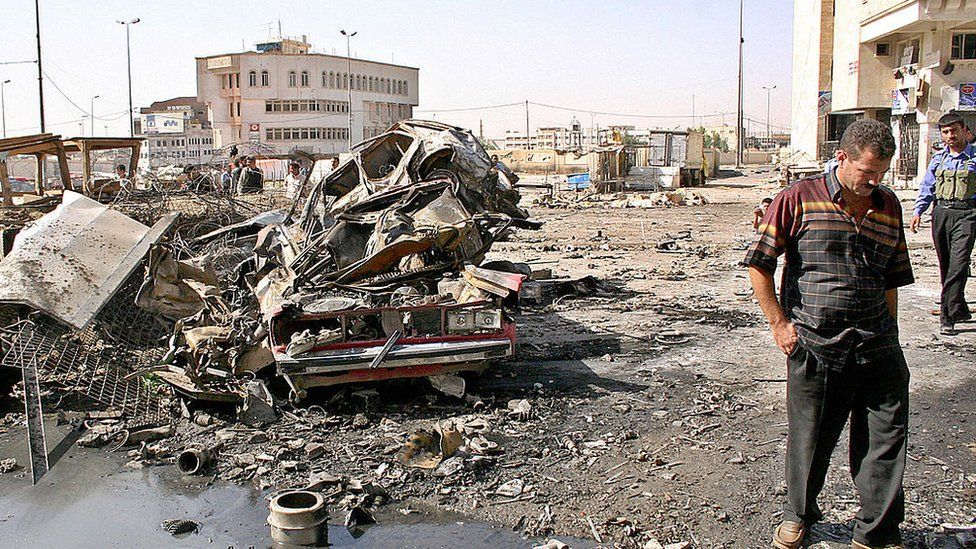An Iraqi civilian inspects damage at a police station that was destroyed in a suicide car bomb attack in Mosul (26 June 2005)