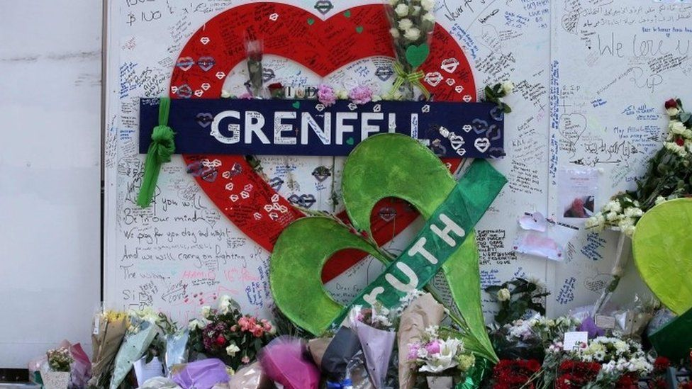 Tributes at a memorial at the base of Grenfell Tower, 2018