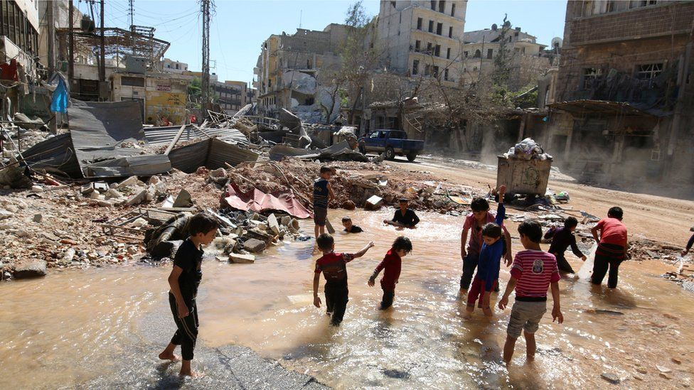 "Children play with water from a burst water pipe at a site hit yesterday by an air strike in Aleppo""s rebel-controlled al-Mashad neighbourhood, Syria, September 30, 2016."