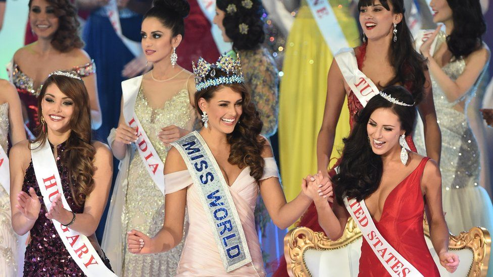 Miss South Africa and the 2014 Miss World, Rolene Strauss (C), dances with first runner up Miss Hungary Edina Kulcsar (L) and second runner up Miss United States Elizabeth Safrit (R) during the grand final of the Miss World 2014 pageant