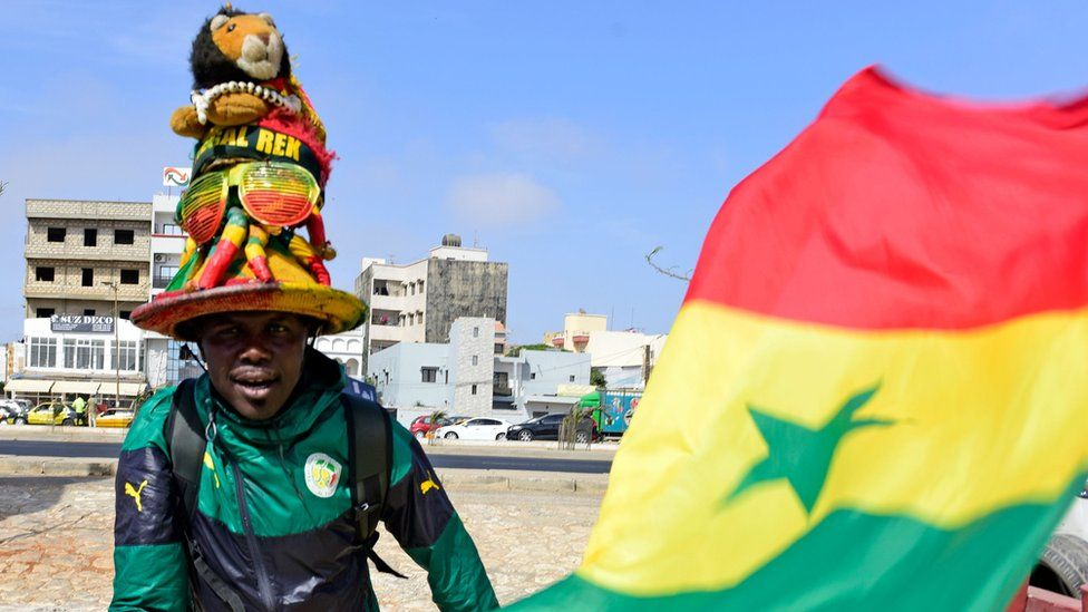 A supporter of Senegal's football team poses with the national flag in Dakar on May 17, 2018, during the announcement of squad members ahead of the forthcoming 2018 FIFA World Cup in Russia