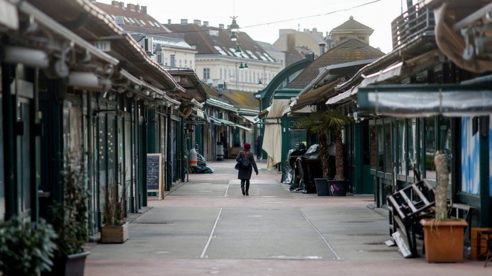 A lone person walks through a deserted street in the Austrian capital Vienna