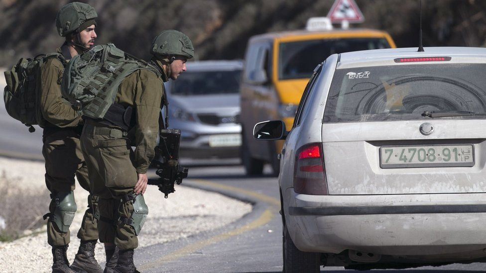 Israeli soldiers speak to a Palestinian driver at a checkpoint near the West Bank city of Nablus on 11 January 2018