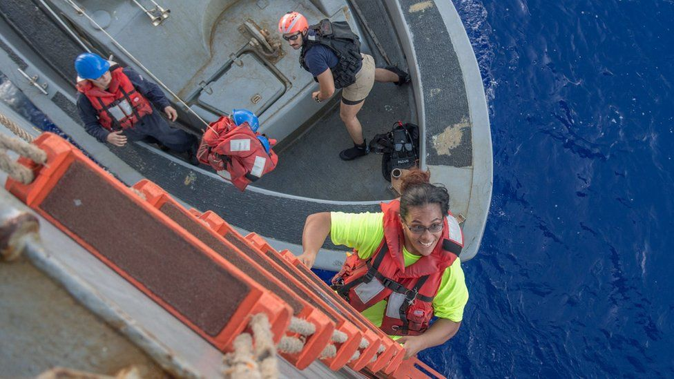 Tasha Fuiava, a US mariner who had been sailing for five months on a damaged sailboat, climbing on board the USS Ashland in the Pacific Ocean, 25 October 2017