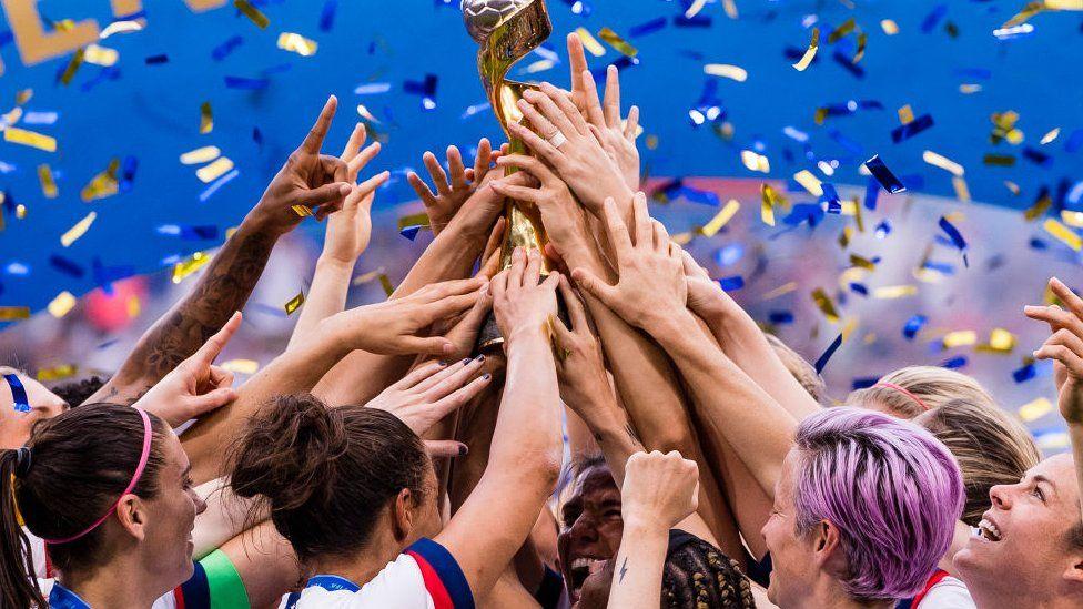 US women's football team holding trophy