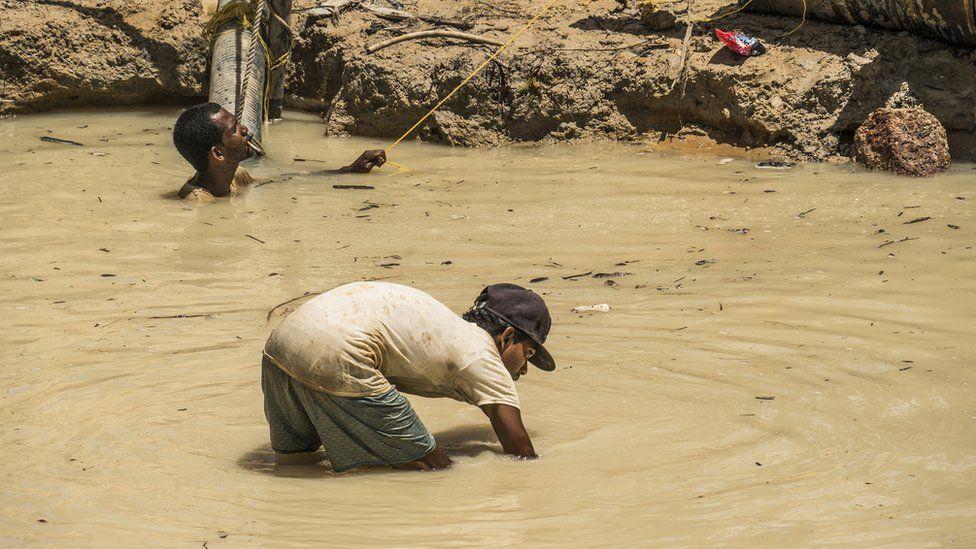 Gold mine workers toil in dirty water in Guyana's Mazaruni region