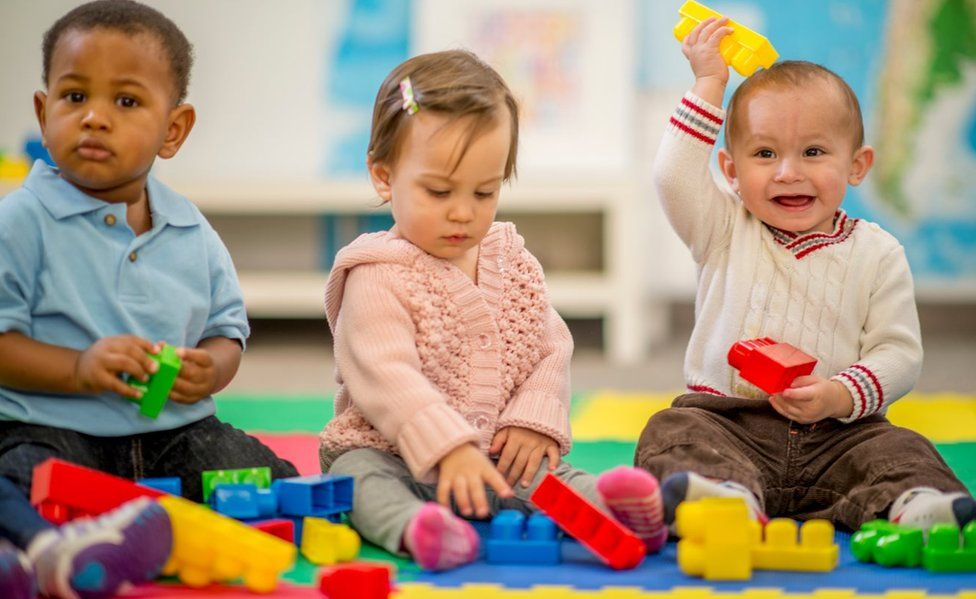 Three young children playing with plastic blocks