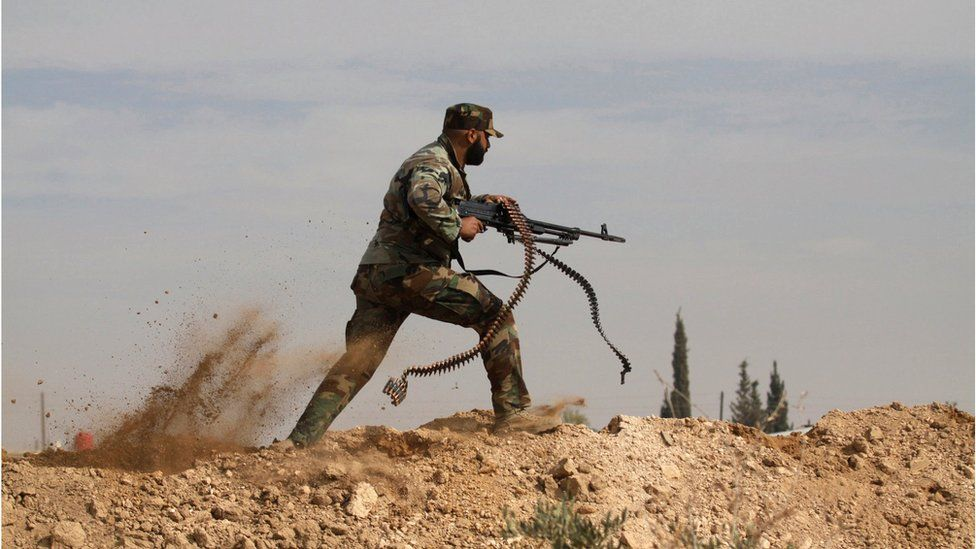 A Shiite fighter carrying a machine gun dodges bullets fired by Syrian rebels in the town of Hatita, outside Damascus, Syria. 22 November 2013.