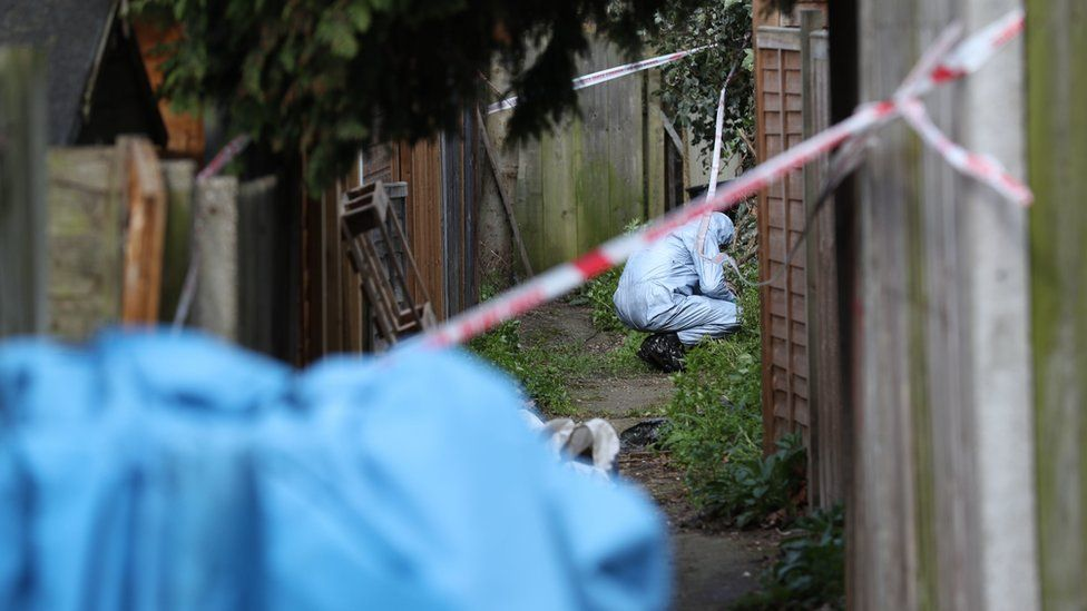 Police forensics officers in an alleyway at the back of properties on Darell Road