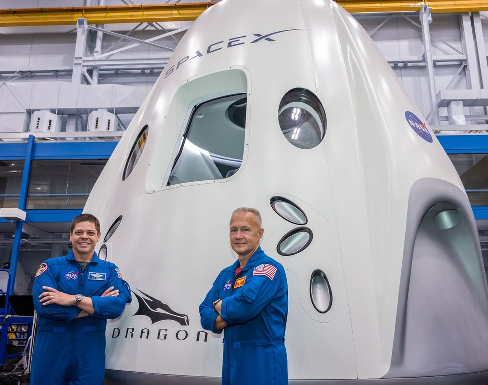 Behnken (L) and Hurley pose for pictures in front of the Crew Dragon