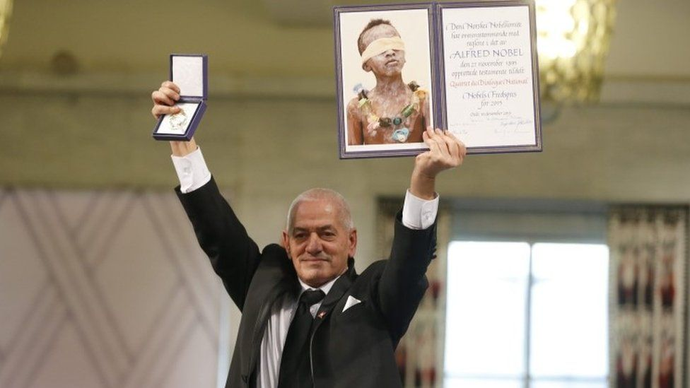 Secretary General of the Tunisian General Labour Union (UGTT) Houcine Abassi poses with the diploma and medallion during the Nobel Peace Prize award ceremony